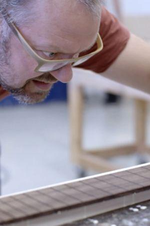 Jonni Roos rakentaa kitaraa ja liimaa kaulaan ruusupuisen otelaudan.