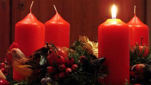 Neljä paksua punaista kynttilää, joista yksi sytytetty, jouluisessa koristekranssissa.