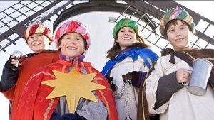 Saksalaiset tiernapojat: neljä itämaan tietäjäksi pukeutunutta n. 10-vuotiasta poikaa hymyilevät aurinkoisesti.