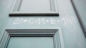 Numerot ja kirjaimet 20 C+M+B+14 liidulla harmaaseen peilioveen kirjoitettuna merkkinä Sternsingerien käynnistä.