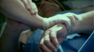Sairaanhoitaja pitää vuoteessa makaavaa potilasta käsivarresta kiinni 1979