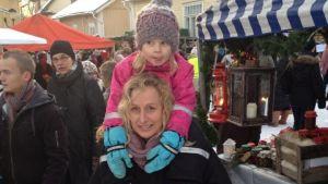 Ulrika Ström med sin dotter på axlarna på en marknad.