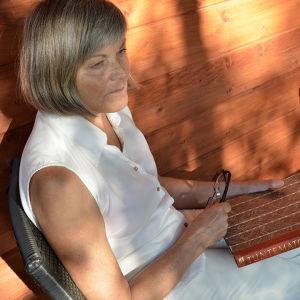 Bloggaaja Marjatta Mentula istuu ilta-auringossa kädessään Tuntematon sotilas -kirja.