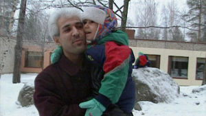 Kurdi-isä lapsensa kanssa talvisella pihalla Suomessa