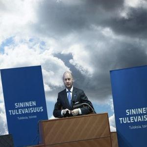 Bildcollage som visar Sampo Terho vid ett podium mot en blå himmel.