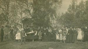 En bild tagen mellan 1910-1929. Anhöriga och vänner tar avsked av den avlidne på gården innan kistans lock sätts på.