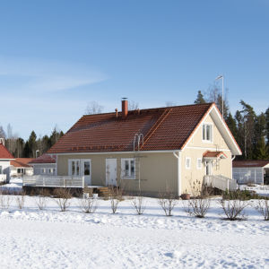 Rätt så nybyggda småhus i ett bostadsområde. Marken är täckt av snö.