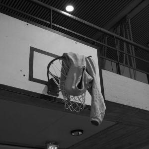En huvtröja hänger från en basketring.