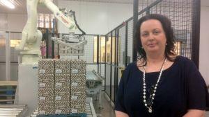 Annika Boström, VD för Boströms bageri, står bredvid en robot som lyfter lådor på plats