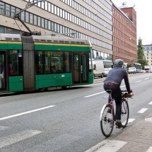 Bilden visar en väg med en cyklist och en spårvagn.