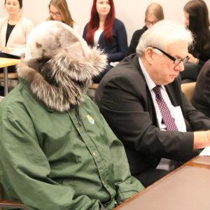 Pekka Seppänen sitter i rättssalen med en grön jacka och huvan framför ansiktet.