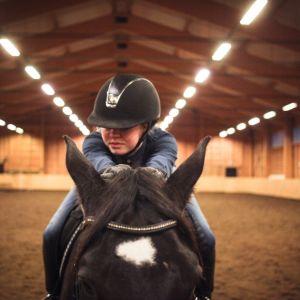 Nainen hevosen selässä.