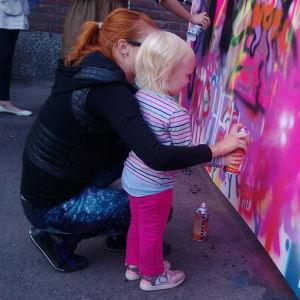 pieni tyttö maalaa seinää spraymaalilla äidin avustamana