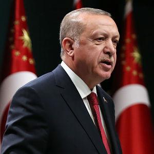 Turkiets president Recep Tayyip Erdoğan står framför en rad med turkiska flaggor.