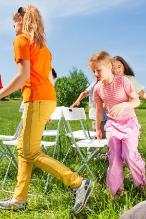 barn leker stolleken på en äng medan Kasper Strömman iakttar med ryggen vänd mot kameran.