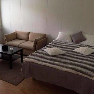 Ett rum med en liten soffa, ett soffbord och en säng. Vid väggen under fönstret står en madrass luad.