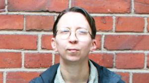 Filosofen Mari Lindman står vid en tegelvägg och ser mot kameran.