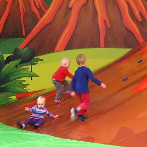 Lapset kiipeävät leikkivuorelle.