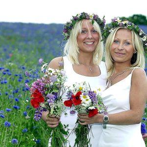 Två unga kvinnor står på en blommande äng med midsommarkransar i håret.