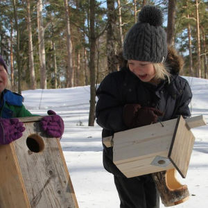 Lapset kantavat linnunpönttöjä talvella