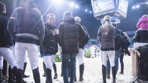kilparatsastajia esteratsastuskilpailuiden katsomossa