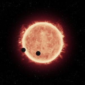En artists bild av två exoplaneter som kretsar kring en röd dvärg