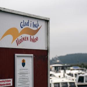 En skylt där det står Glad i Ingå på svenska och finska. I bakgrunden syns båtar i en småbåtshamn,