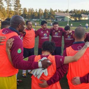 FC Slimmits spelare samlade i en ring före en match.