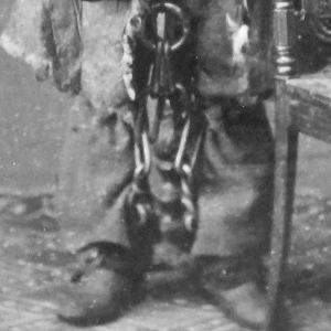 Ett gammalt svartvitt fotografi. Man ser benen och fötterna på en man. Han är fastkejdad med tunga kedjor.