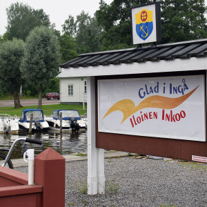 En skylt där det står Glad i Ingå på svenska och finska. I bakgrunden syns en småbåtshamn.