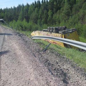 Påhängsvagn på taket i dike vid söndrigt vägräcke på motorväg.