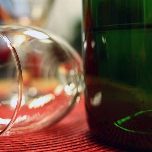 Viinipullo ja tyhjä viinilasi kaatuneena