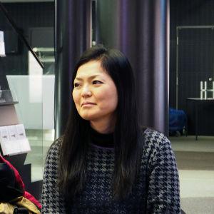 Minamin äiti Emi Yoshida seuraa haastattelua taustalla. Emi on ammatiltaan kalligrafi.