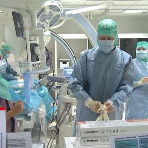 Kirurg drar på sig skyddsutrustning i en operationssal.