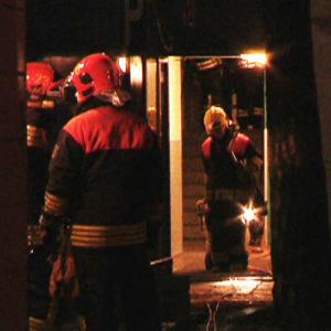 Brandmän i trapphuset i det branddrabbade höghuset i Nordsjö i Helsingfors.