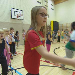 Elever klasserna ett till sex kastar boll i gymnastiksal