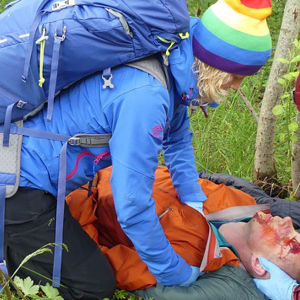 två personer i vildmarken hjälper en tredje som fått en skallskada, simulerd bild