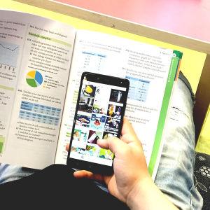 En person som sitter i en soffa med en skolbok framför sig och en mobil i andra handen.