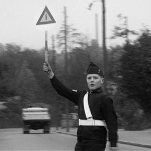 Univormuasuinen koulupartiolainen pysäyttää liikenteen suojatiellä.