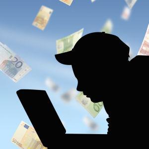 Silhuett av en person som sitter vid en dator, pengar flyger i bakgrunden.
