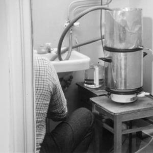 Mies keittää pontikkaa asuntonsa vessassa.