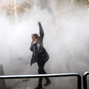 Iranilaisnainen suojasi kasvonsa kyynelkaasulta mielenosoituksessa Teheranin yliopistolla 30. joulukuuta.