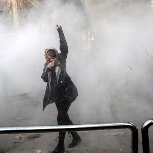 Iranilaisopiskelija yrittää suojautua kyynelkaasulta mielenosoituksessa