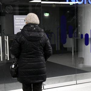 Nainen suljetun Nordea-konttorin edessä.