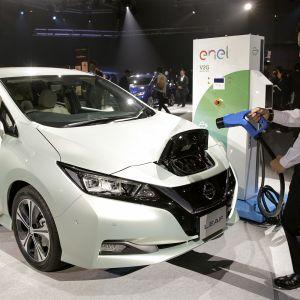 Henkilökunta esittelee miten sähköautoa ladataan Tokion Makuhari -messuilla lokakuussa 2017.