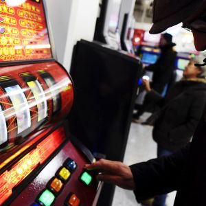Mies pelaa peliautomaattia marketissa.