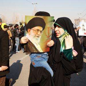 Iranilaisnainen lapsineen hallintoa tukevalla marssilla Teheranissa 5. tammikuuta 2018. Naisen kädessä Iranin hengellisen johtajan Ali Khamenein kuva.