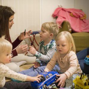 Nainen leikkii kolmen pikkulapsen kanssa lattialla