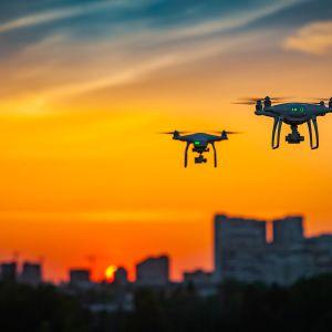 Kaksi dronea lentää iltaruskossa.