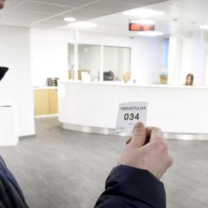 Mies jonottaa työvoimatoimistossa Helsingissä.